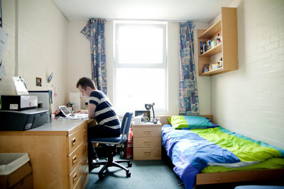 Male student working on laptop in his bedroom in Darwin College