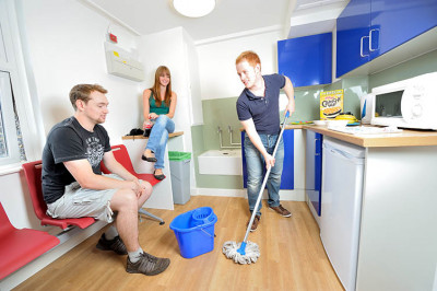 Three students cleaning and talking in Keynes College kitchenette