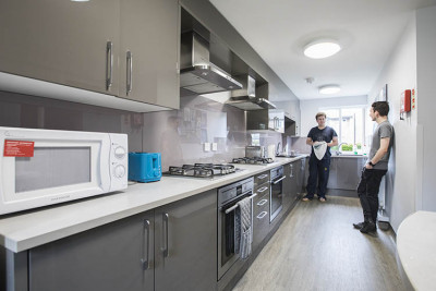 Two male students chat and wash up in a Park Wood House kitchen