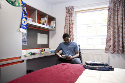 Student reading in a Tyler Court bedroom