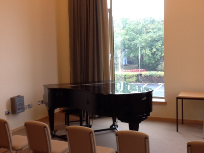 Piano by a window in one of the practice rooms