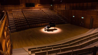 Spotlight on a piano in the Colyer-Fergusson Concert Hall. Image: Molly Hollman